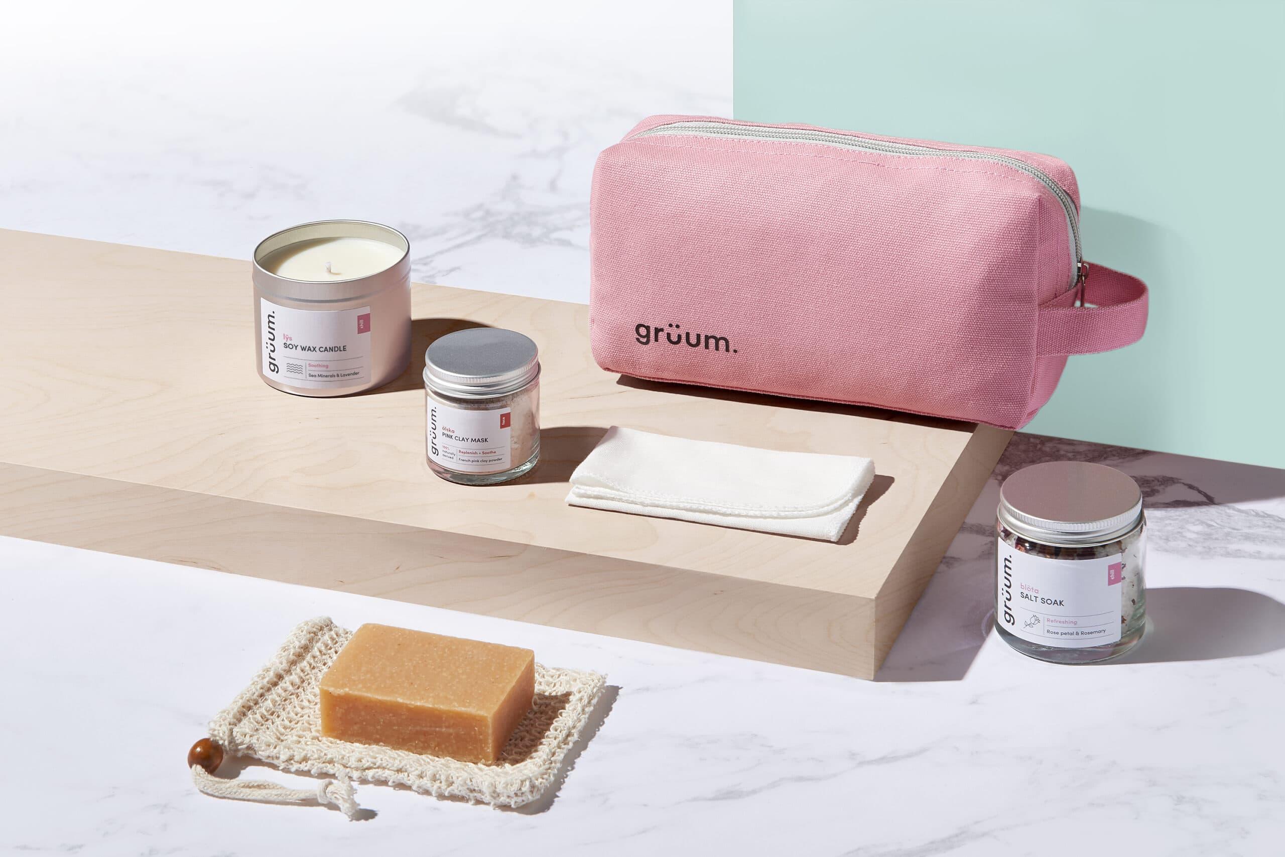Gruum product image with washbag, soy wax candle, pink clay mask, bolta salt soak, body bar, sisal soap bag and muslin cloth